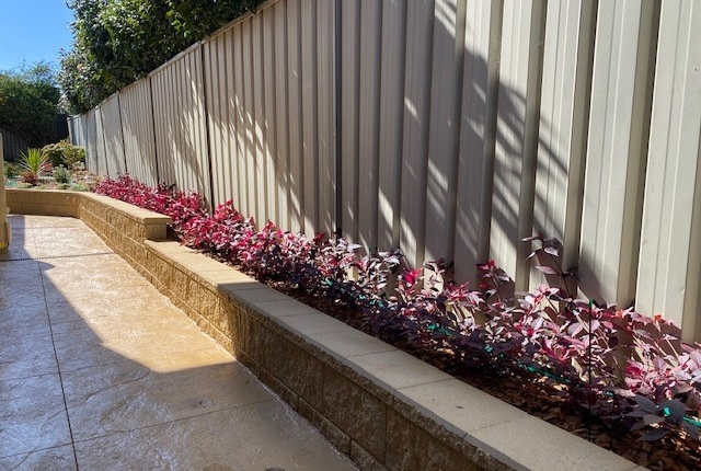 Retaining wall and garden bed against fence in Kings Langley